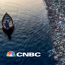 Person in rowboat next to large pile of trash in sea from CNBC